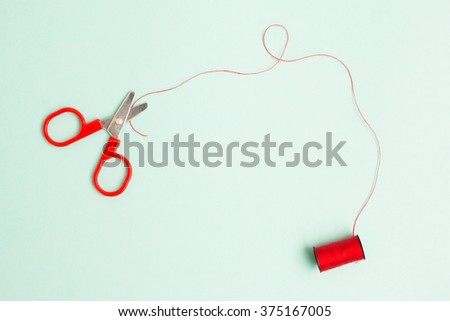 Scissors are cutting red thread on light blue background. - stock photo