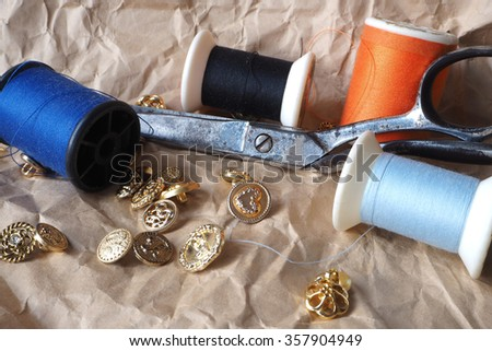 Scissors, bobbins with thread and buttons on the old wooden background - stock photo