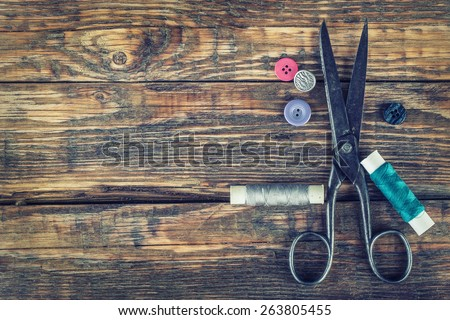 Scissors, bobbins with thread and needles. Old sewing tools on the old wooden background. Vintage Background - stock photo