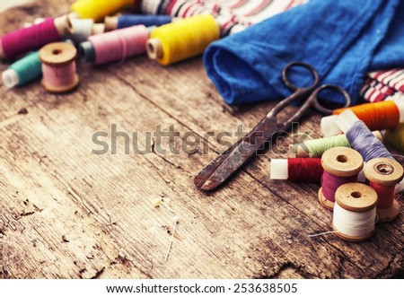 Scissors, bobbins with thread and needles, striped fabric. Old sewing tools on the old wooden background. Vintage Background - stock photo