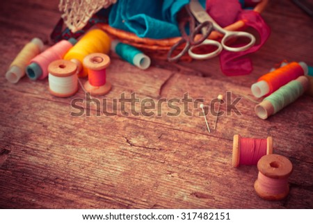 Scissors, bobbins with thread and needles, striped fabric. Old sewing tools on the old wooden background. Vintage Background. - stock photo