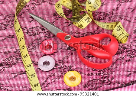 Scissors, buttons, measuring tape and pattern on fabric - stock photo