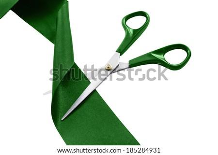 Scissors cut green silk ribbon on white background - stock photo