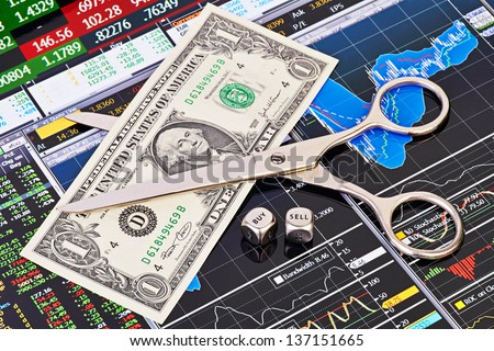 Scissors cutting  one-dollar banknote, dices cubes with the word SELL BUY. Financial charts and columns of prices as background. Selective focus - stock photo
