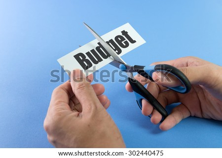 Scissors cutting paper with the word budget on it - stock photo
