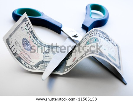 Scissors cutting through dollar note on white background - stock photo