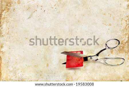 Scissors cutting up a credit card on a grunge background. Copy-space for your text. - stock photo