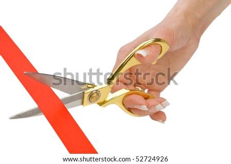 Scissors in a female hand cut a red tape - stock photo