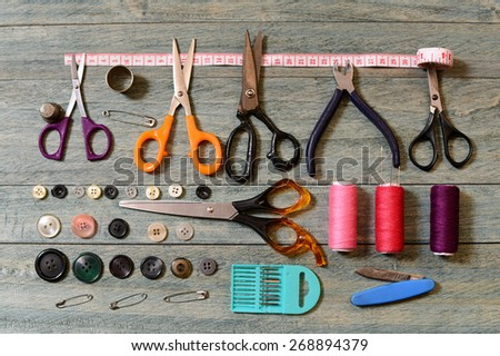 Scissors, thread, buttons and needles for sewing on the table - stock photo