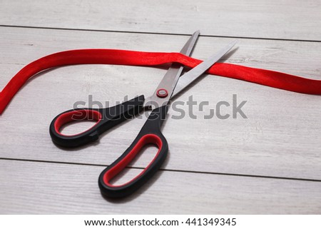 Scissors with red handles cut red tape. Red tape is lying on wooden background. - stock photo
