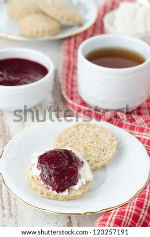 Scone with goat cheese and jam, cup of tea for breakfast - stock photo