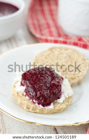 Scone with goat cheese and jam, cup of tea for Breakfast closeup vertical - stock photo
