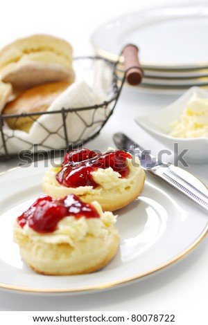 scone with strawberry jam and clotted cream , afternoon tea , cream tea , tea party, buttermilk biscuits - stock photo