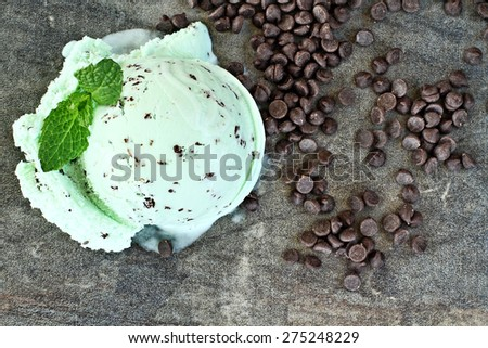Scoop of delicious chocolate chip mint ice cream with mint leaves and chocolate chips. - stock photo