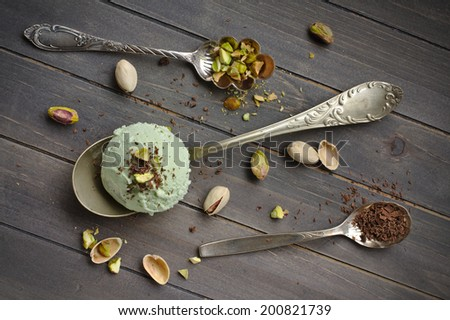 Scoop of homemade pistachio ice cream with chopped pistachios and chocolate on old wooden backgroung - stock photo