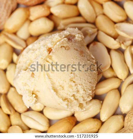 Scoop of peanut butter ice cream with peanuts from above - stock photo