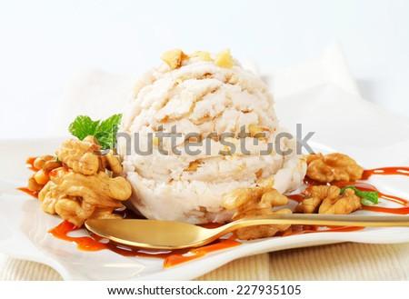 Scoop of walnut ice cream with caramel sauce - stock photo