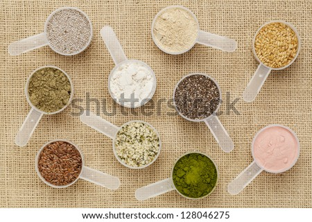 scoops of superfood - healthy seeds and powders (white and black chia, flax, hemp, pomegranate fruit powder, wheatgrass, hemp and whey protein, maca root) on canvas - stock photo