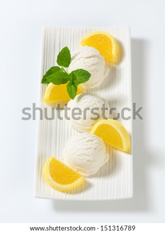 Scoops of white ice cream decorated with fruit jelly on a porcelain tray - stock photo