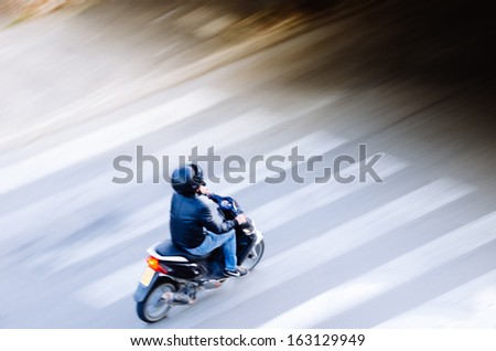 Scooter driver entering a black area to conquer challenge concept. Panned shot with background motion blur. - stock photo