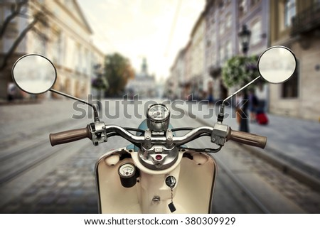 Scooter on foregrounf and blurred view on city on background - stock photo