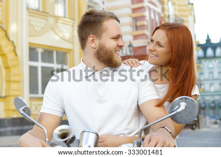 Scooter ride. Portrait of a bearded young man holding a handlebar and a red-haired girl looking at each other smiling, both wearing white shirts, old city on the background - stock photo