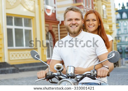 Scooter ride. Portrait of a bearded young man holding a handlebar and a red-haired girl sitting behind him smiling, both wearing white shirts, old city on the background  - stock photo