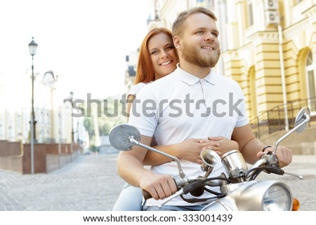 Scooter ride. Portrait of a happy smiling couple riding a retro scooter, bearded man holding a handlebar driving, while his red-haired girlfriend looking at the camera happily - stock photo