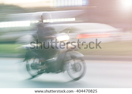 scooter rider on a bike lane in the busy city traffic in motion blur, filtered with retro colors - stock photo