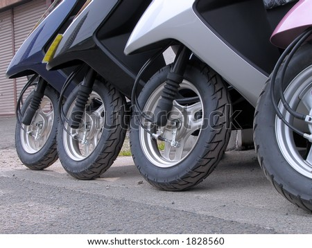 Scooter wheels in a row in front of a urban motorcycle shop.