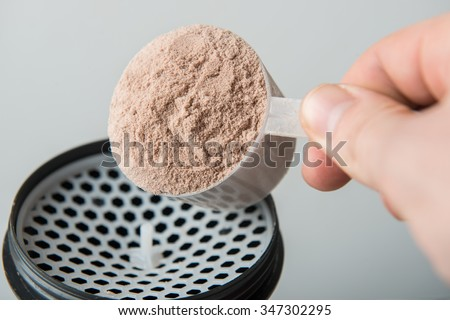 Scope of chocolate whey isolate protein next to the translucent protein shaker, with focus on the protein inside the scoop - stock photo