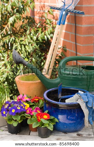 Scope of garden equipment and pansy flower in a spring garden - stock photo