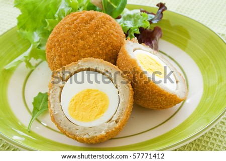 Scotch eggs on a plate with a green salad - stock photo