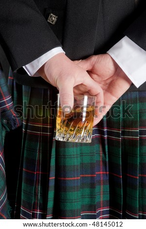 Scotsman holding his glass of whisky behind is kilt - stock photo