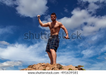 Scottish bearded man in a skirt standing on a hill against beautiful sky background menacingly waving a steel dagger
