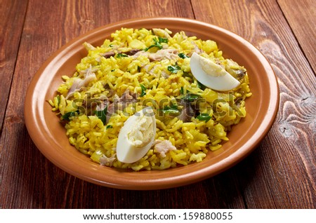 Scottish dish - Kedgeree, flakes of smoked herring baked with rice, milk,  parsley, and served with hard-boiled eggs.   - stock photo