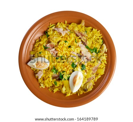 Scottish dish - Kedgeree, flakes of smoked herring baked with rice, milk,  parsley, and served with hard-boiled eggs.  isolated  - stock photo