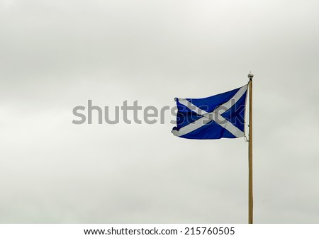 scottish flag against overcast skies - stock photo