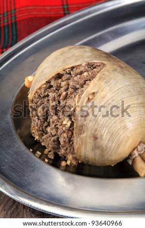 Scottish Haggis Cooked For A Burns Night Dinner Against A Royal Stuart Tartan - stock photo