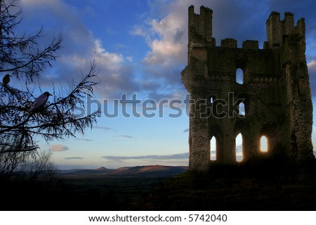 Scottish Haunted Tower at Dusk with rolling Hills in background, glowing shafts of light through lower windows and Crows nesting in turret and in Fir Tree in forground - stock photo