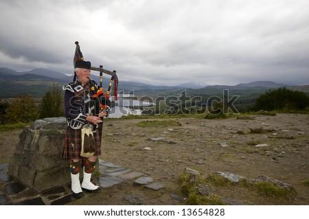 Scottish highland piper in full military regalia - stock photo