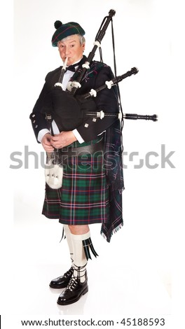 Scottish highlander wearing kilt and playing bagpipes - stock photo