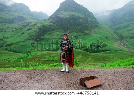 SCOTTISH HIGHLANDS - Piper in traditional Scottish on bagpipes and three sister of Glencoe in Scottish Highlands, United Kingdom on June 28, 2016 - stock photo