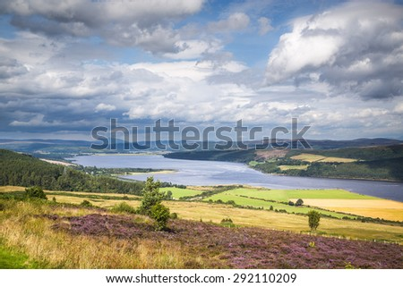 Scottish landscape, with a river and flourished fields surrounded by clouds. - stock photo
