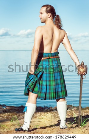 Scottish man with sword near the sea - stock photo