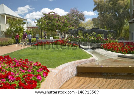 SCOTTSDALE, ARIZONA - CIRCA 1990's: A sculpture of running horses and beautiful spring flowers in Old Town of Scottsdale, Arizona - stock photo