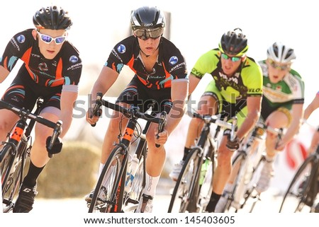 SCOTTSDALE, AZ - MAY 19: Domenic Suozzi (center) leads the pack during the Criterium at DC Ranch, a high-speed circuit race on a 1-kilometer closed course on May 19, 2013 in Scottsdale, AZ.  - stock photo
