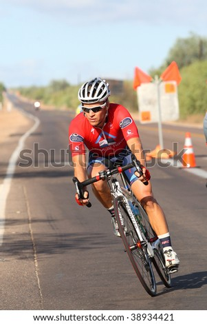 SCOTTSDALE, AZ - OCTOBER 4:A racer makes the turn after a 10 mile downhill in the 6th annual Tour de Scottsdale, a charity bicycle race on Saturday October 4, 2009 in Scottsdale Arizona - stock photo