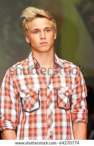 SCOTTSDALE, AZ - OCTOBER 8: Male Model showcasing music inspired apparel from Fender Musical Instruments Corporation at the Phoenix Fashion Week runway shows on October 8, 2010 in Scottsdale, AZ. - stock photo