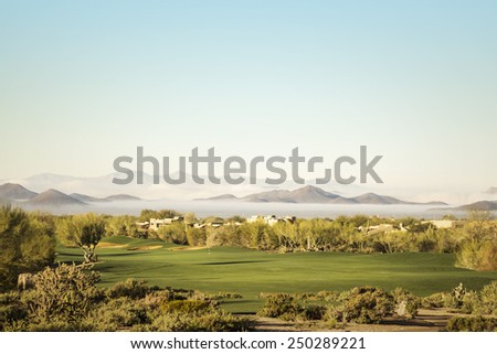 Scottsdale, Phoenix area golf course with dramatic unusual low lying fog in below mountain peaks in distance - stock photo